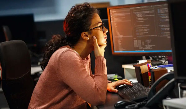 woman working at desk with multiple screens